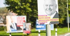 """Vordergrund: Wahlplakat der FDP an Laternenmast (Bundestagwahl 2017, Slogan: """"Gute Ideen brauchen Freiheit); Hintergrund unscharf: Großflächenplakate mit SPD-Kanzlerkandidat Martin Schulz"""